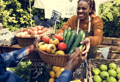 Woman selling produce at farmers market